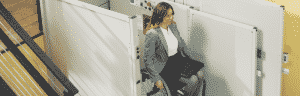 executive woman on wheelchair smiling getting off vertical platform lift