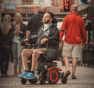 Man on the street using Invacare power wheelchair