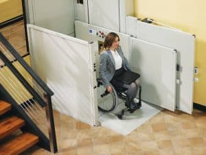 woman in wheelchair smilling using outdoor vertical residential platform lift at bottom