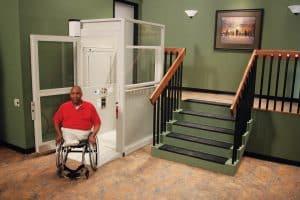 man in wheelchair using vertical platform lift