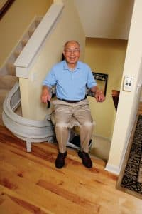 man smiling while using curved stair lift in middle of stairs