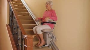 Senior woman using stair lift in middle of stair