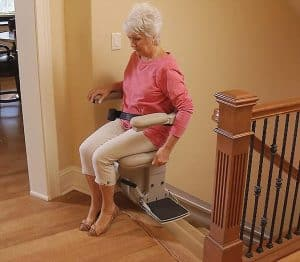 woman using stair lift at top stairs
