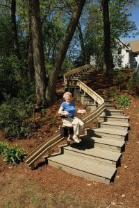 Senior woman while seated on outdoor curved stair lift at bottom of stair