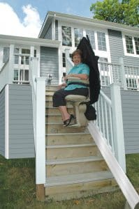 woman while seated on outdoor stair lift at middle of stair