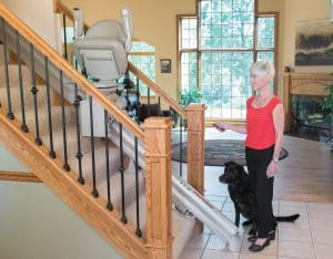 standing senior woman next to black dog with remote control in hands pointing to stair lift