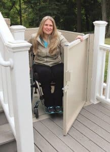 woman in wheelchair using outdoor vertical residential platform lift at top