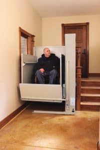 man in wheelchair using vertical commercial platform lift