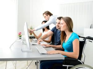 young female worker on wheelchair with coworker in business office working on a desktop computer