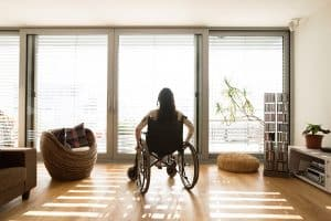 rear view of woman in wheelchair at home looking at window