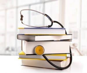 stack of books with stethoscope on the table in library