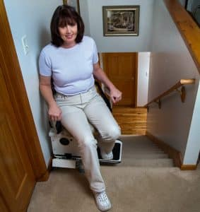 woman at the top of stairs while stair lift is at top of stairs