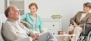 elderly couple talking with younger woman while senior woman is on wheelchair