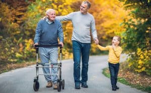 senior using mobility device with family