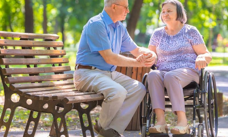 couple at the park. woman on wheelchair