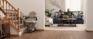 stair lift at the bottom of stairs with African Americans couple in background on the couch smiling