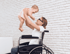 woman in wheelchair holding up baby
