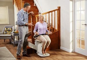 Couple talking next to a power stair lift