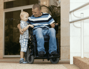 man in wheelchair with arms around stading child