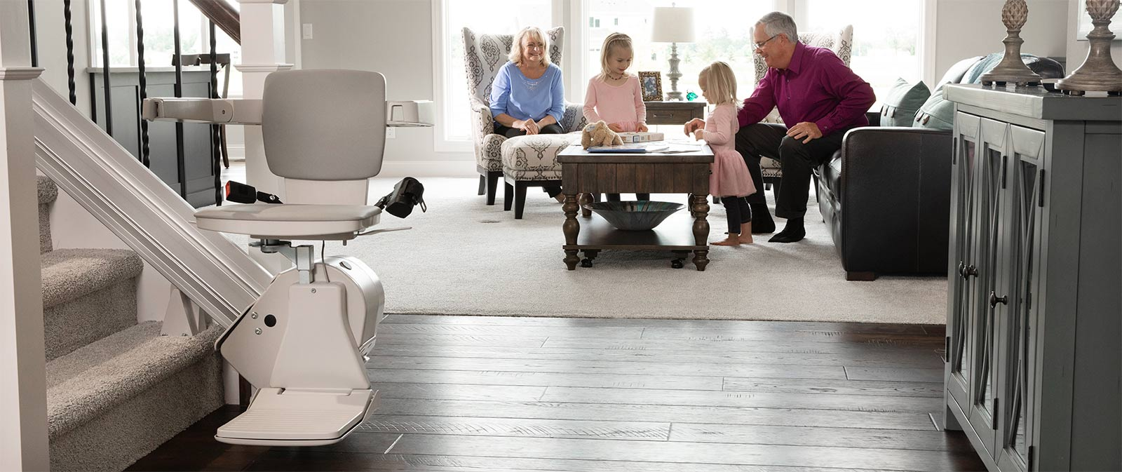 stair lift at the bottom of stairs with senior couple with children in background on the couch smiling